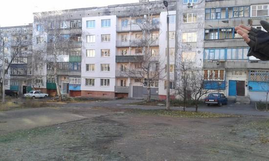 Разрушенные при обстрелах блоки панельных домов заменяют новыми. В соседних квартирах живут люди.